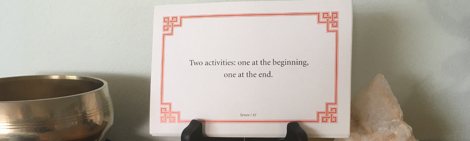 """Lojong card that reads """"Two activities: one at the beginning, one at the end"""" sitting on a wooden shrine with an unpolished chunk of quartz to the right and a meditation bowl to the left."""