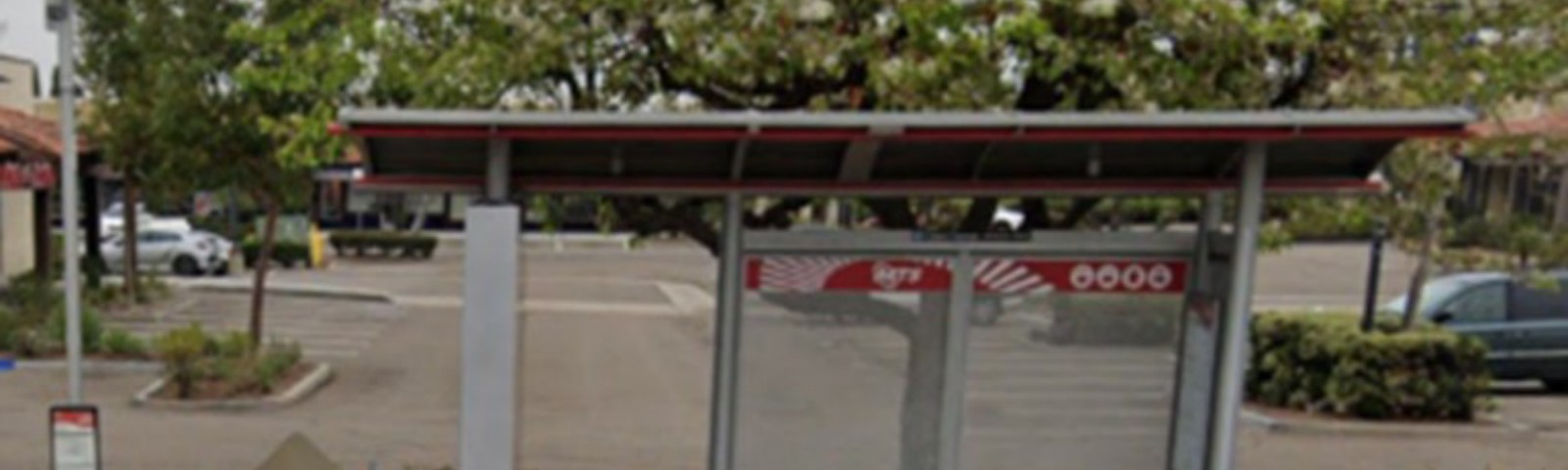 Silver San Diego MTS bus stop. Orange & white cones & construction A-frame to the left. Brown & grey sidewalk in front.