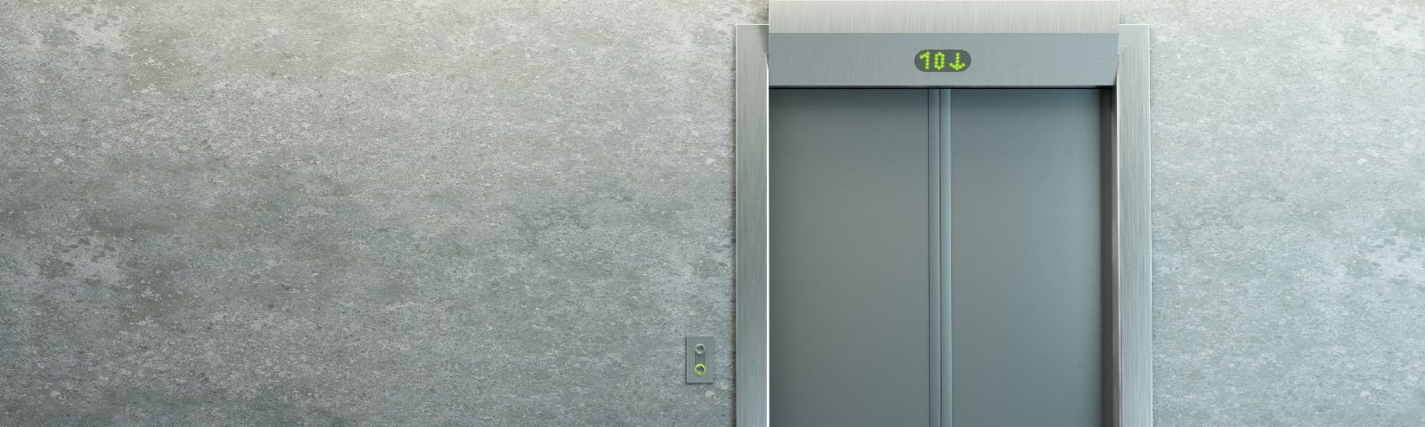The closed door of an elevator against a grey wall