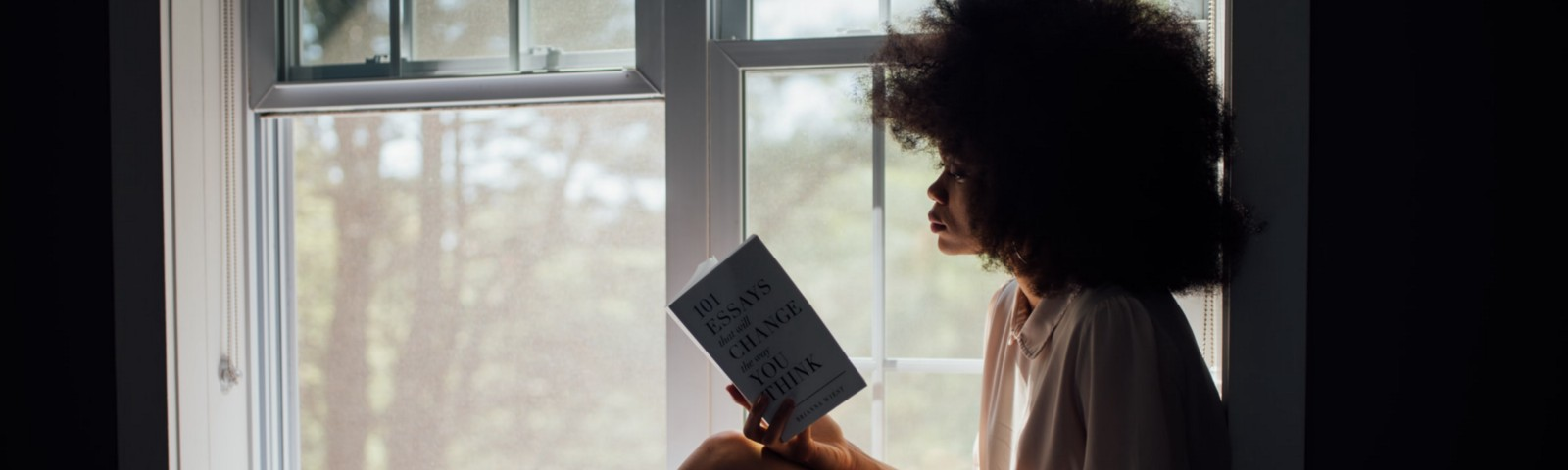 A girl reading a book by the window.