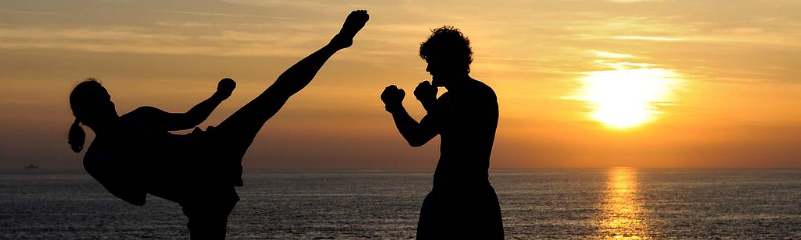 A photo of two people kickboxing at sunset.