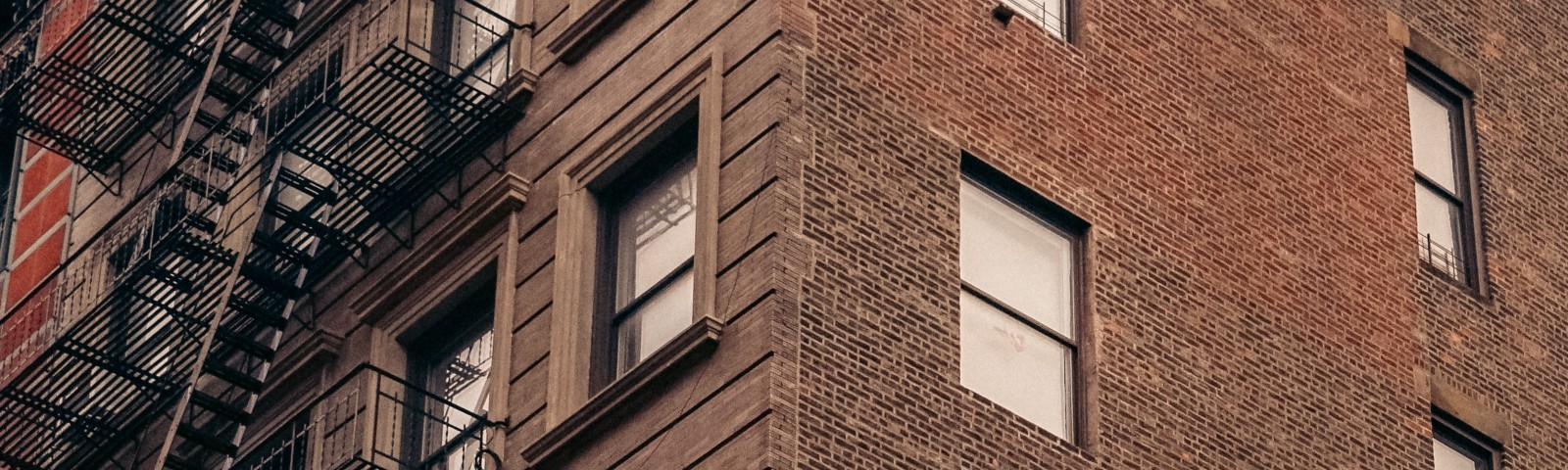 """Brick building with a sign that says """"How Are You, Really?"""""""