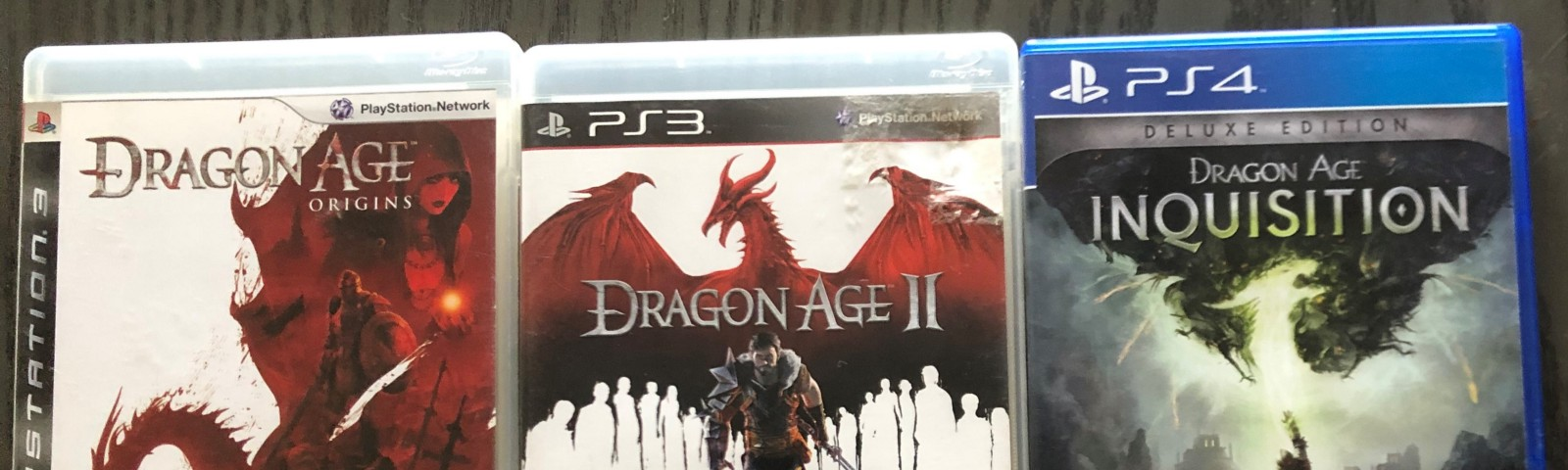 The game cases for Dragon Age: Origins, Dragon Age II, and Dragon Age: Inquisition