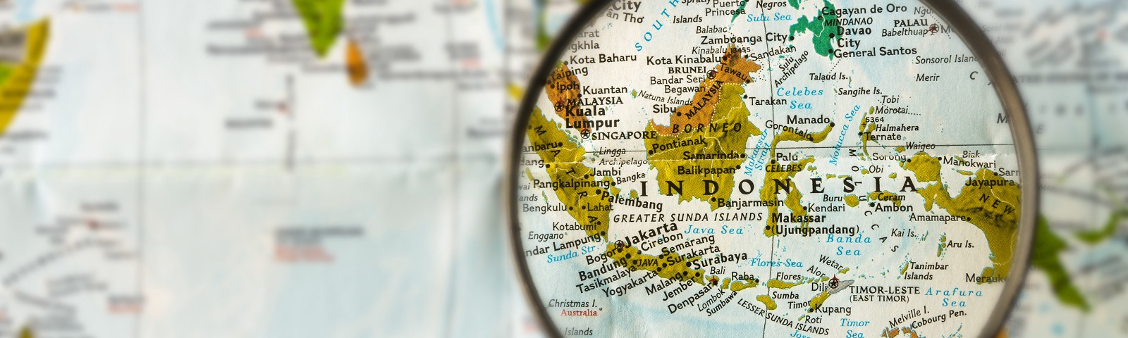 World map with magnifying glass focused on Indonesia