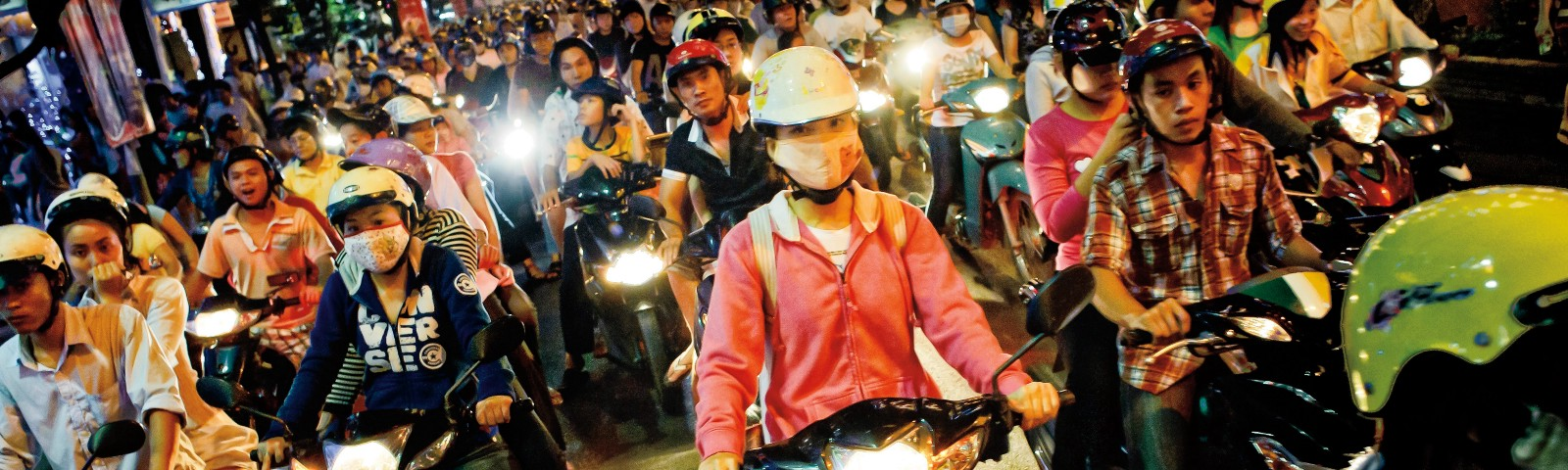 A crowd of people in motorbike traffic, some wearing face masks
