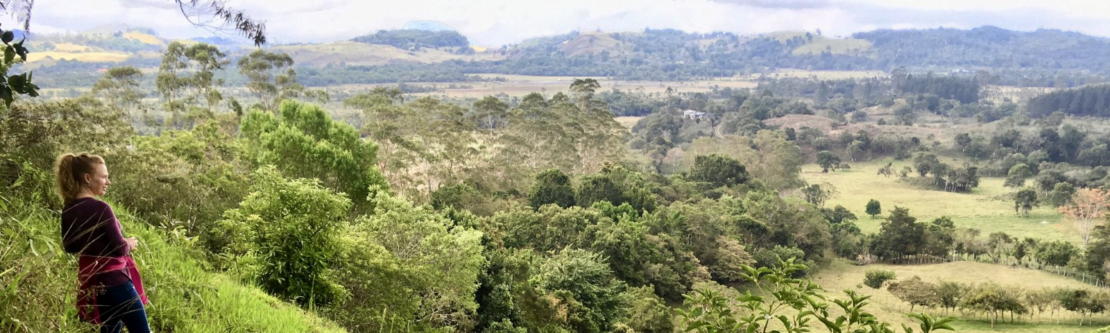 Woman stands on Panama hillside looking out over landscape. personal development mental health retire early life lessons