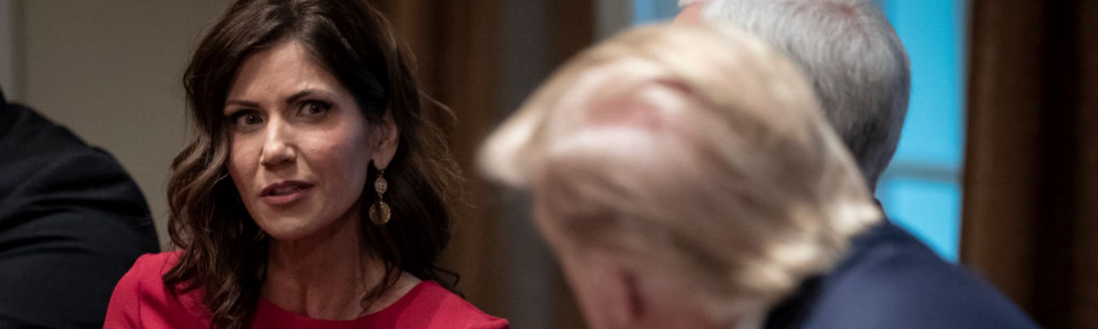 A photo of Kristi Noem talking to Mike Pence and Donald Trump at a meeting.