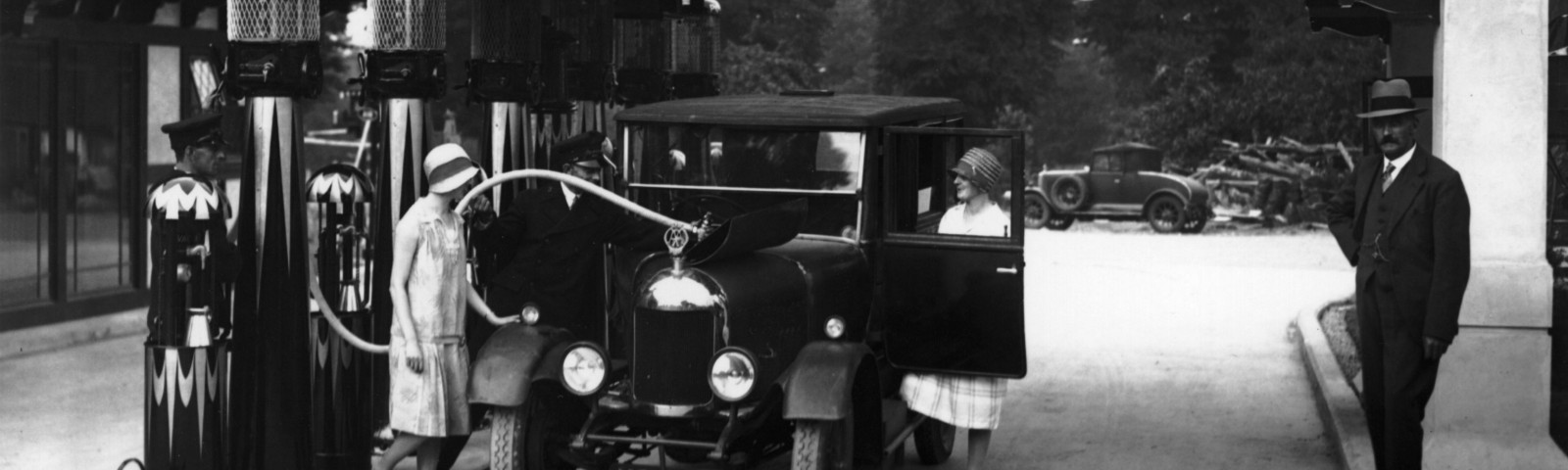 A woman's car being filled up at a petrol station in 1929.
