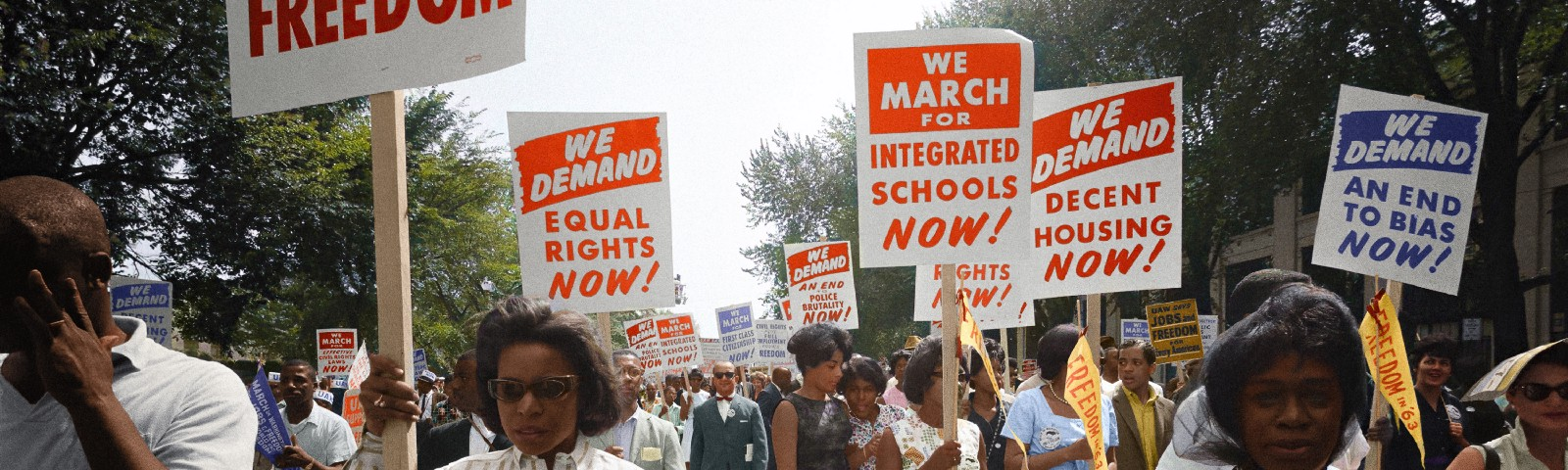 """Civil rights march on Washington, D.C. on August 28th, 1963. Women in foreground hold up signs reading: """"we demand equal rights now, we march for integrated schools now, we demand an end to bias now, and we demand decent housing now."""""""
