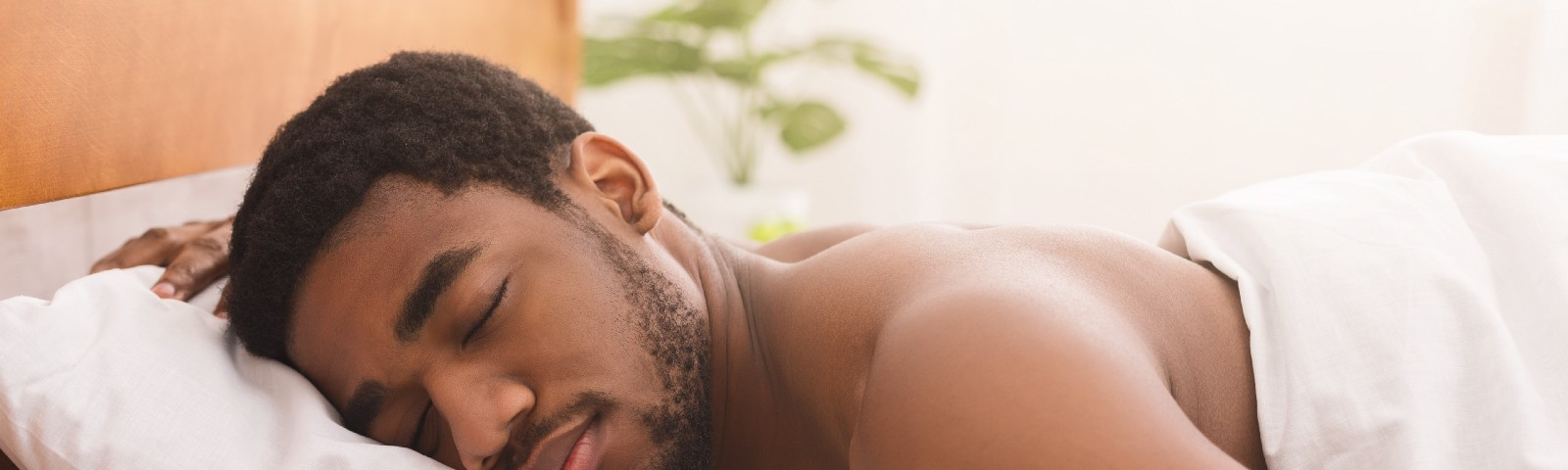 An African-American man sleeping naked under the covers on his stomach in bed at home.