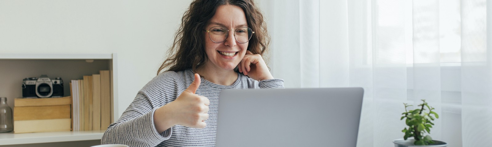 A person with long hair sitting at a laptop next to a window, smiling and awkwardly giving a thumbs-up to the camera.