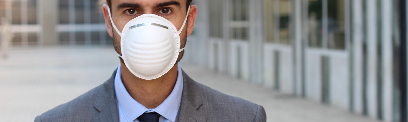 Businessman in suit wearing protective flu mask.