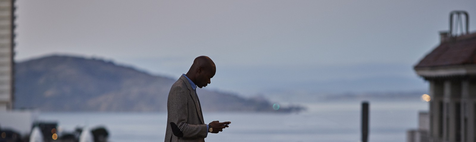 Black businessman checking phone while on the street in San Francisco in the evening.