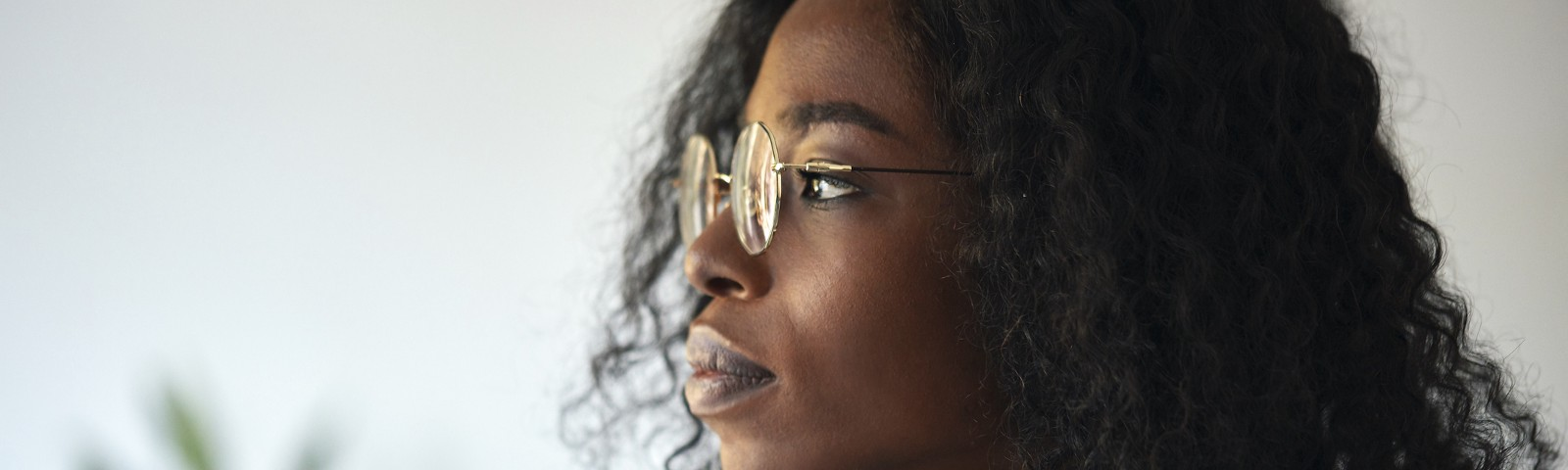 A black businesswoman wearing glasses and a green blazer looks outside.