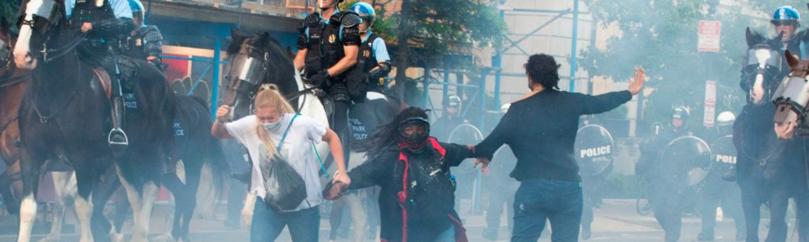 A photo of police tear gassing protestors as the police ride on horses past them.