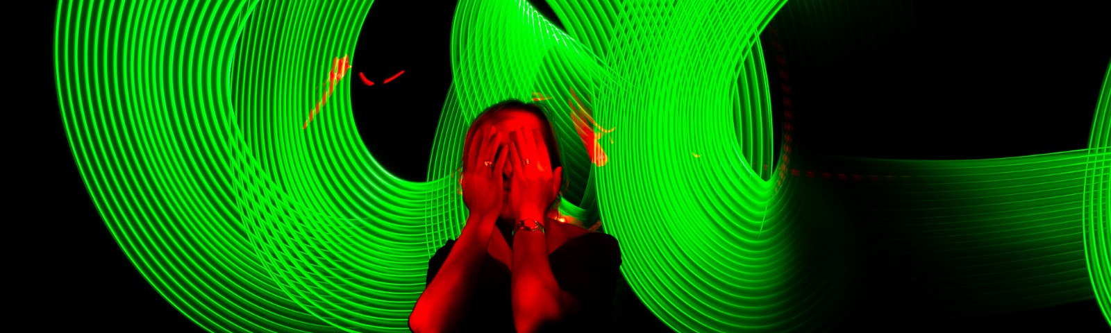 A photo of a person covering their face with their hands. They are illuminated red, and there are green circles around her.
