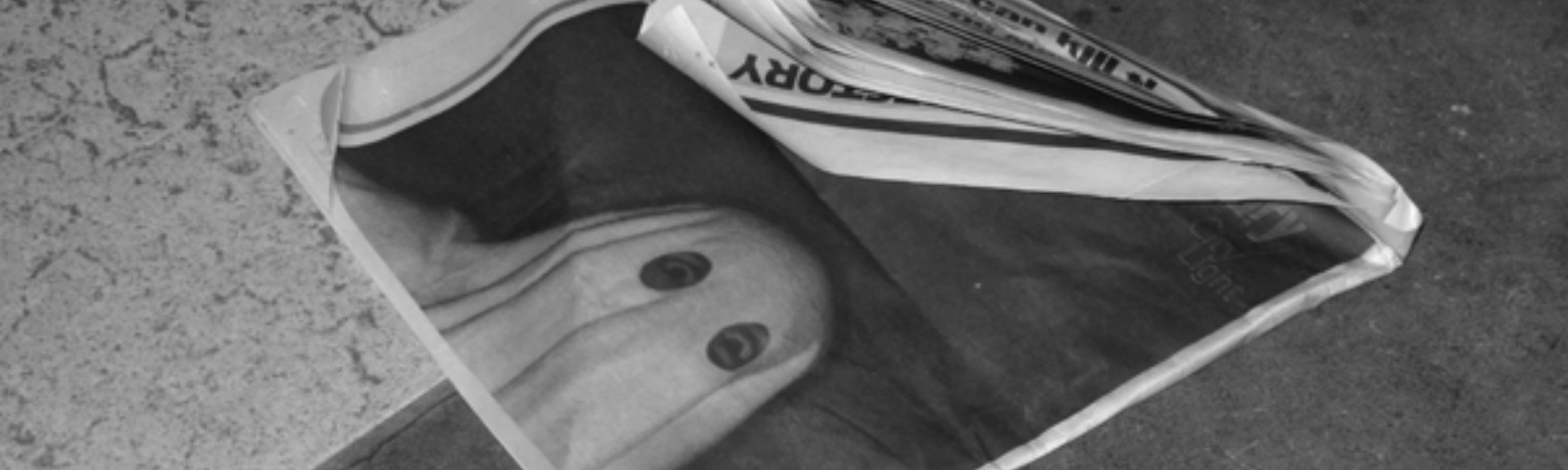 A black and white photo of a newspaper with a picture of a person wearing a ghost sheet over their face.