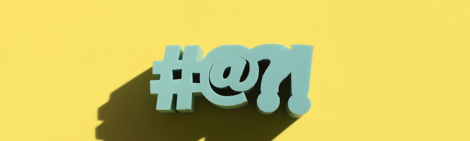 #@?! in block letters against a yellow background.