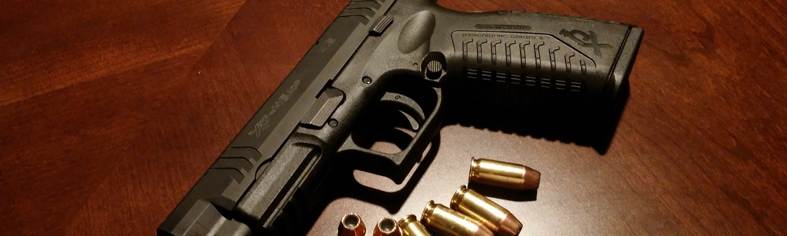 Handgun on wooden table with 7 bullets.