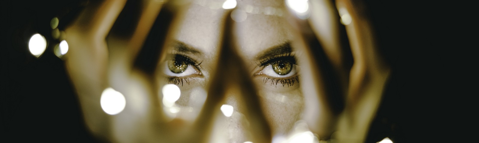 A person's eyes seen through a gap in the fingers, draped with twinkle lights, they hold in front of their face.