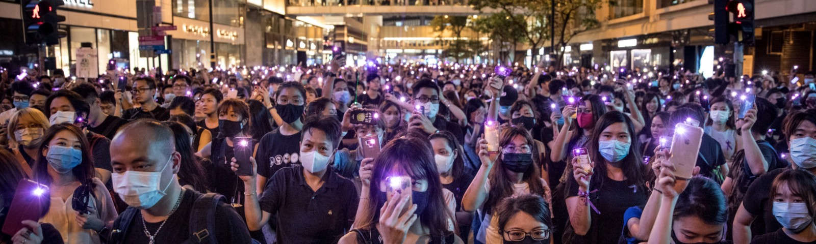 Protesters wave their phones in the air during a rally against police sexual harassment on August 28, 2019, in Hong Kong.