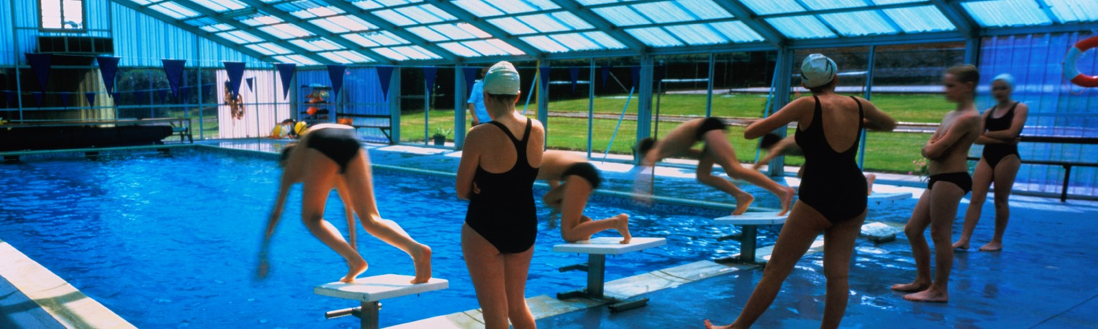 Photo of teenage schoolchildren using indoor swimming pool