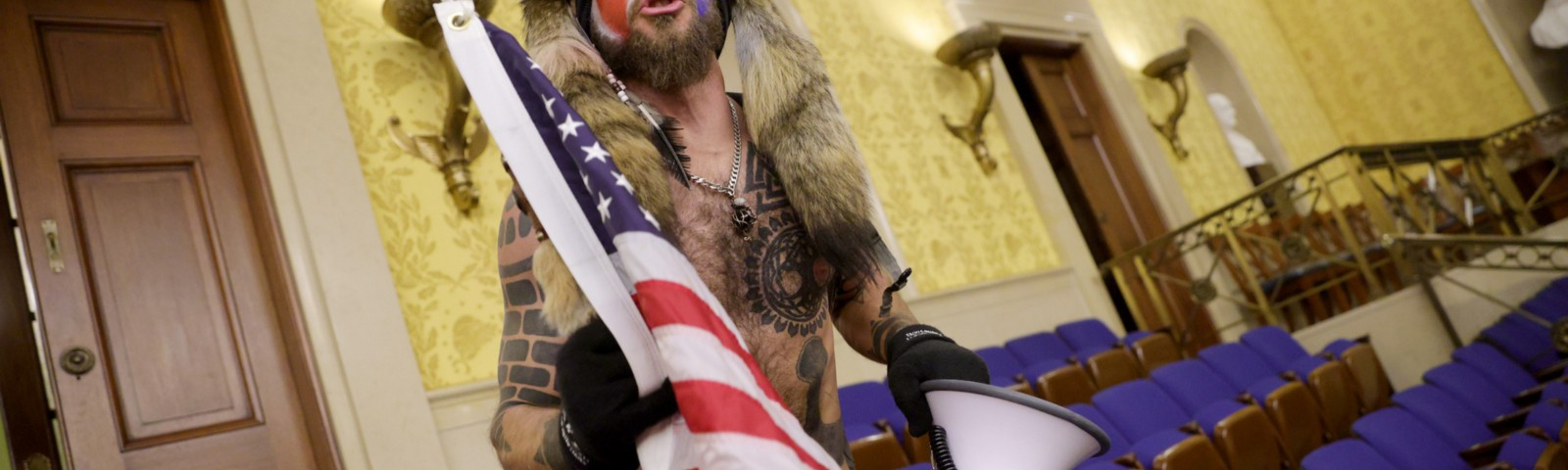 "The ""Qanon Shaman"" wearing fur and a horned hat, holding a US flag and bullhorn in the Capitol building."