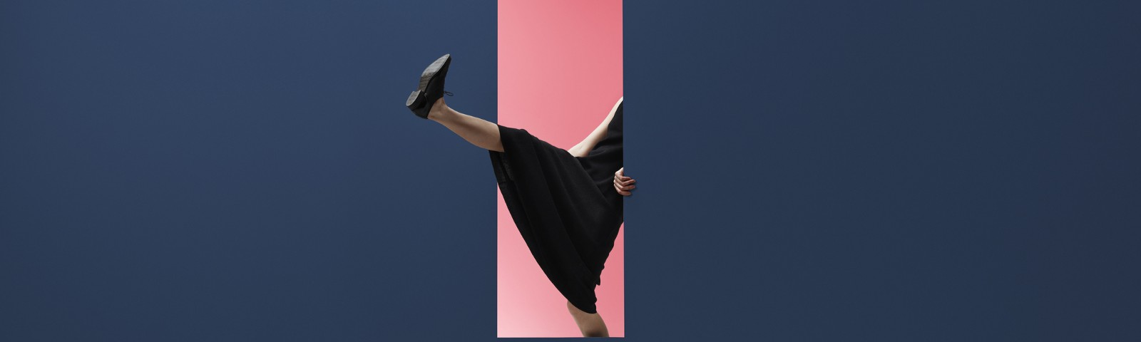 Woman stepping through an opening in the wall, head not visible, her leg in the air.