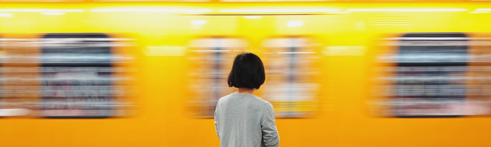 A woman standing in front of a yellow passing subway train. She is also wearing a yellow dress.