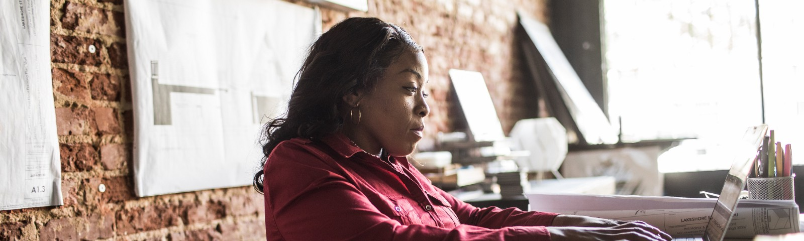A Black businesswoman in a wheelchair works at her desk.
