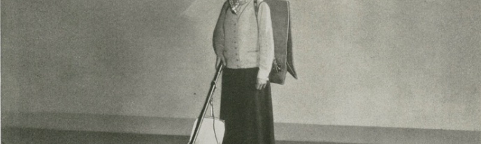 A person wearing a gas mask that connects to a bag on their back uses an upright vacuum on a carpet with a rectangular grid.