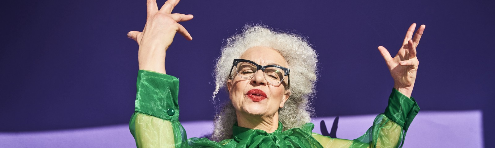 Confident senior woman in green against a violet background throwing up a confident pose.