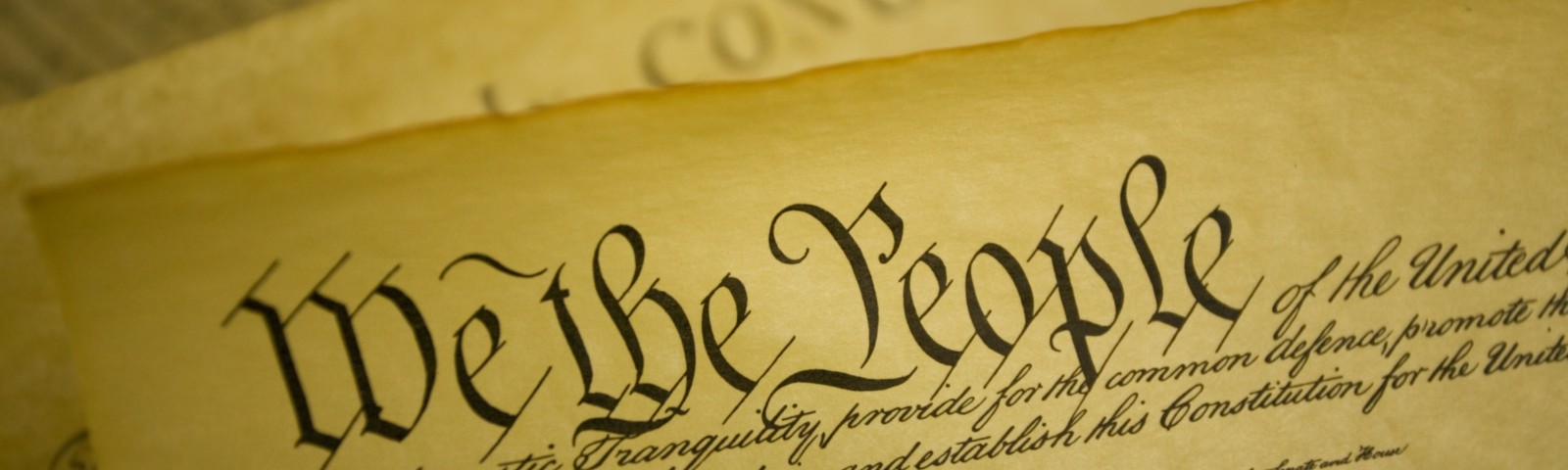 """The Constitution of the United States with """"We the People"""" written in a large, ornate font."""