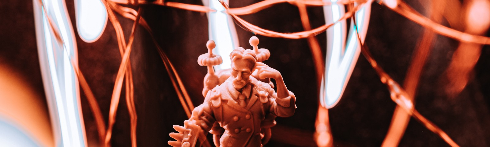 Nikola Tesla as a miniature from the board game, Monumental wrapped in fairy lights with long exposure LEDs in the background