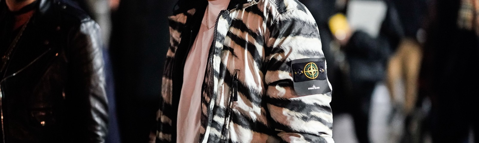 "A man wears a black and white zebra print bomber jacket from the brand ""Stone Island."""