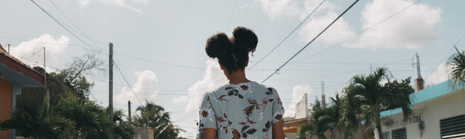 Back view of a young woman walking down a street.
