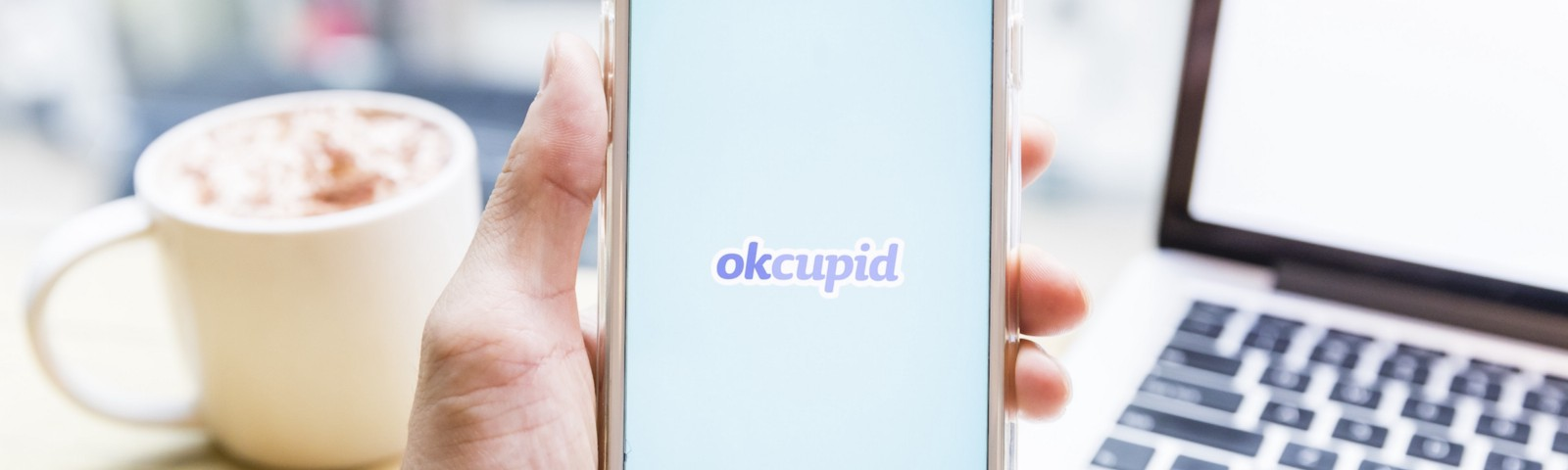 A hand holding a phone with the dating app OkCupid on its screen.