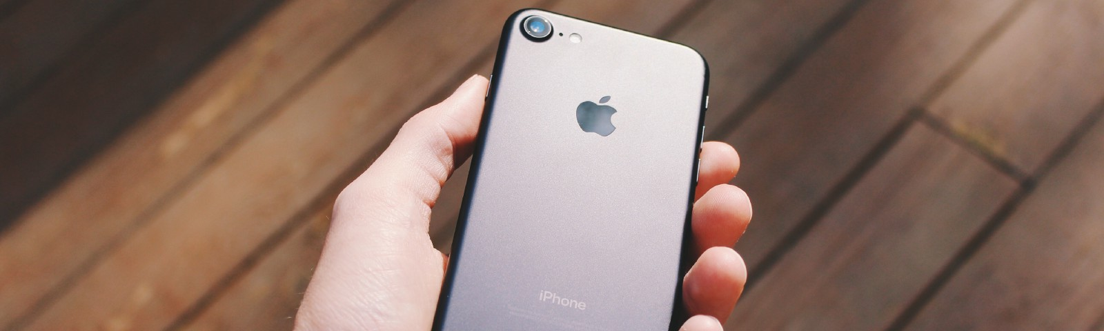 A hand holding an iPhone 6 (its back faces the camera)