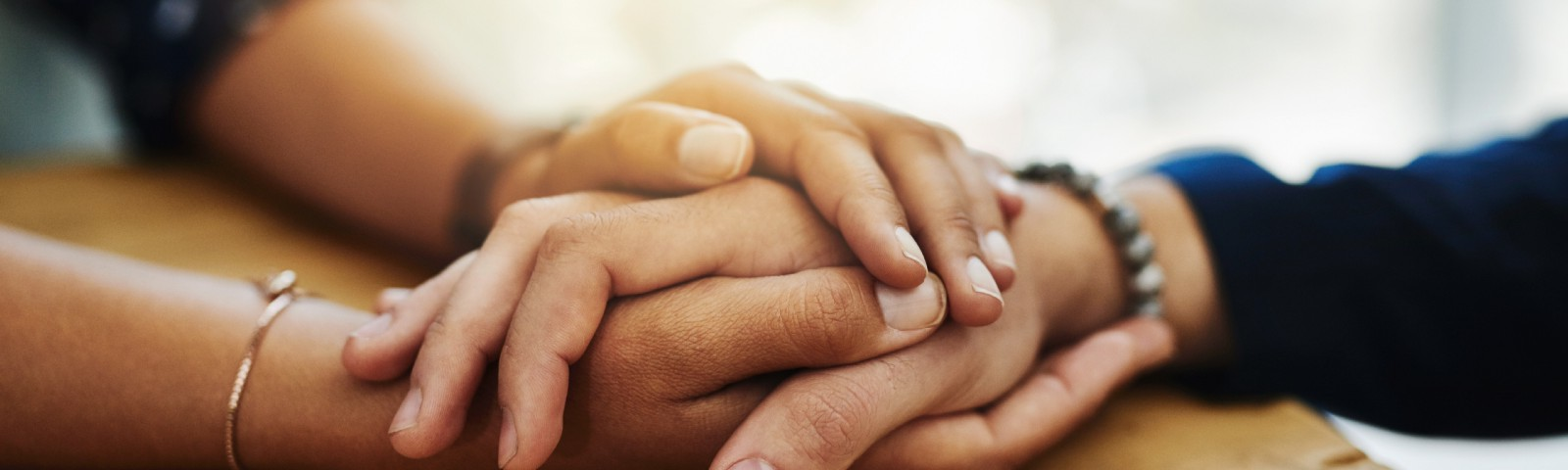 A closeup shot of two unrecognizable people holding hands in comfort