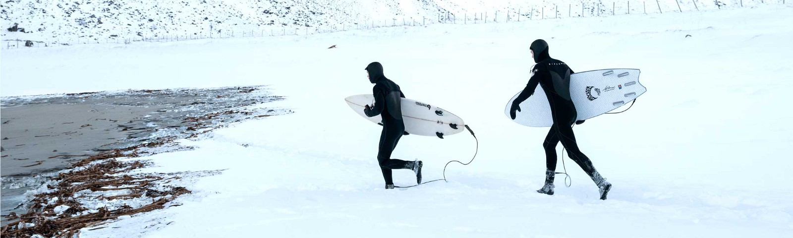 Surfers run across the snow toward Unstad beach in Norway.