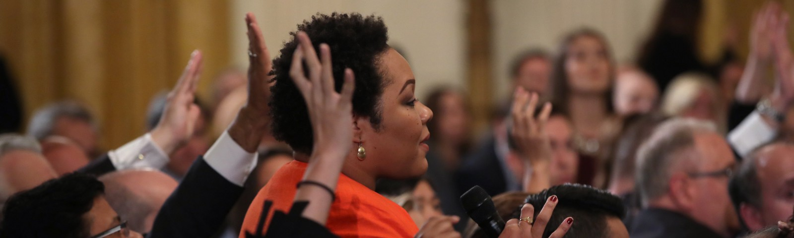 A photo of Yamiche Alcindor asking Trump a question at a press briefing.