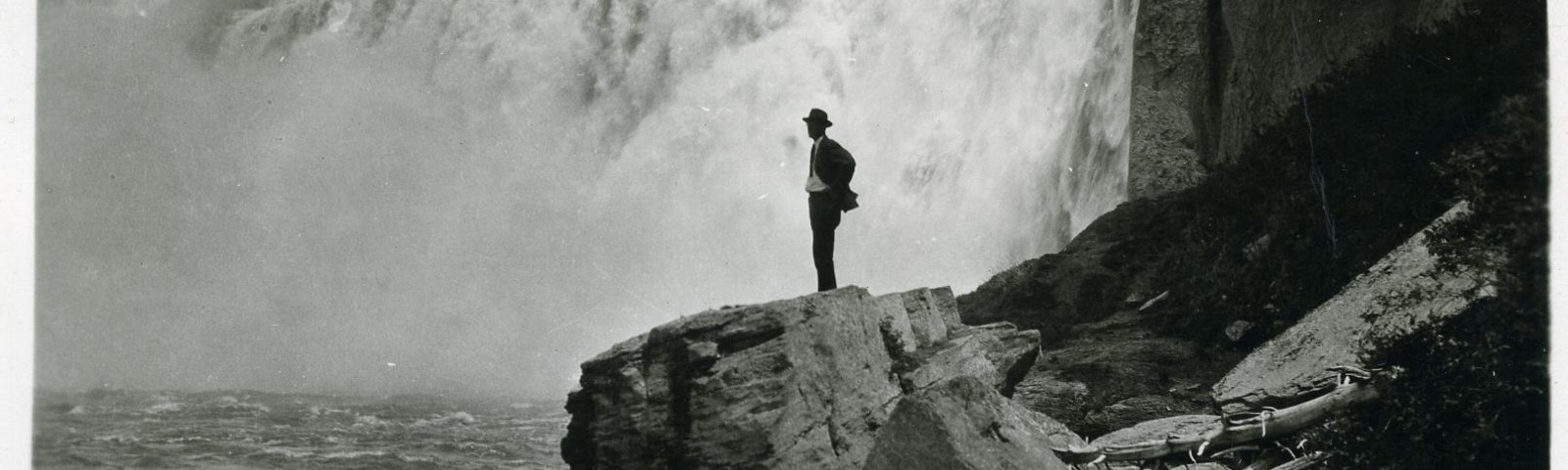 Vintage black-and-white photo of a person standing in front of waterfall.