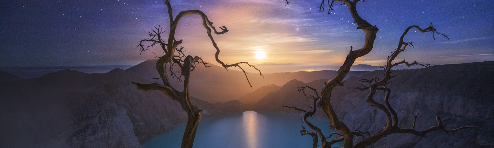 A fine art photograph of bare tree branches framing a moon and lake setting with purple clouds and stars