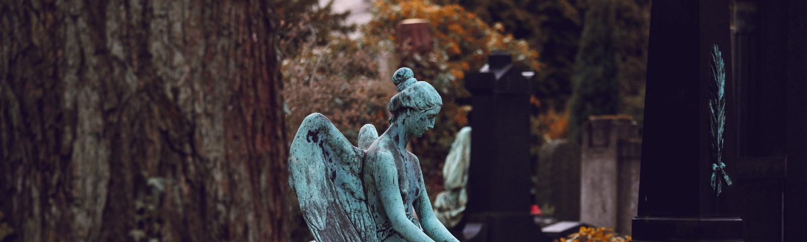 Statue of an angel sits on a tombstone in a cemetery—head bowed down, hands in lap.
