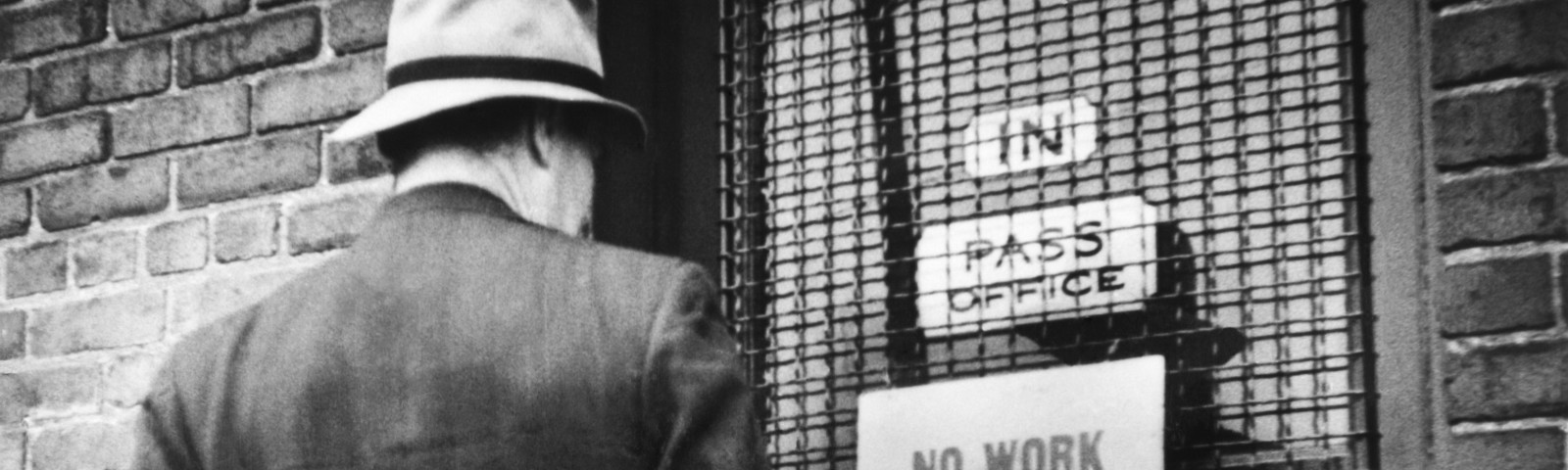 A black and white archival photo of a man standing in front of a door. The sign on the door says: 'NO WORK. DON'T APPLY.'