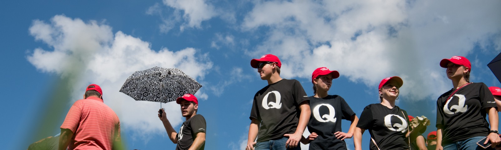 Supporters of President Donald Trump wearing 'QAnon' t-shirts wait in line before a campaign rally at Freedom Hall on 10/1/18