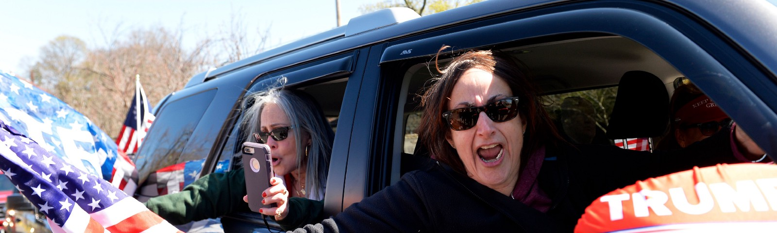 """A photo of anti-shutdown protestors protesting from their car. Two white women hold US flags and """"Trump 2020."""""""