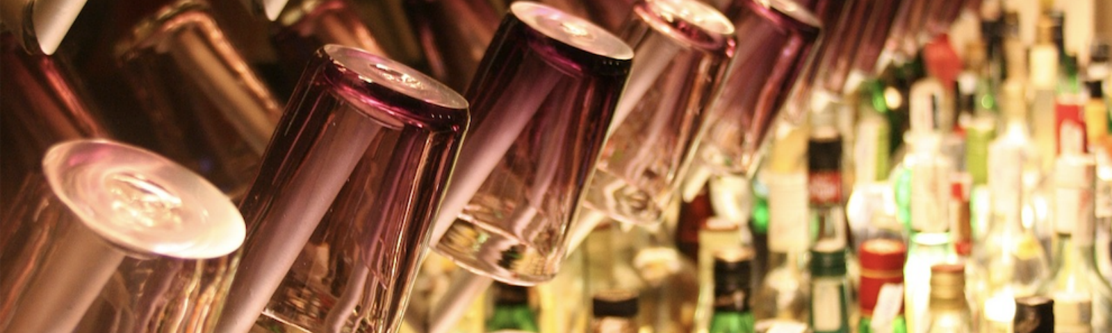 Rows of purple glasses hanging off the wall of a bar, with many liquor bottles below them.