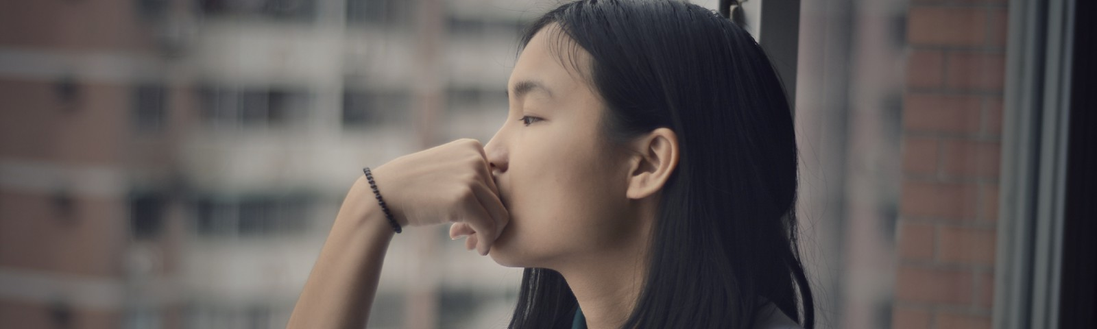 A young woman leans on a railing, with her hand next to her face, as she looks out the window in deep thought.