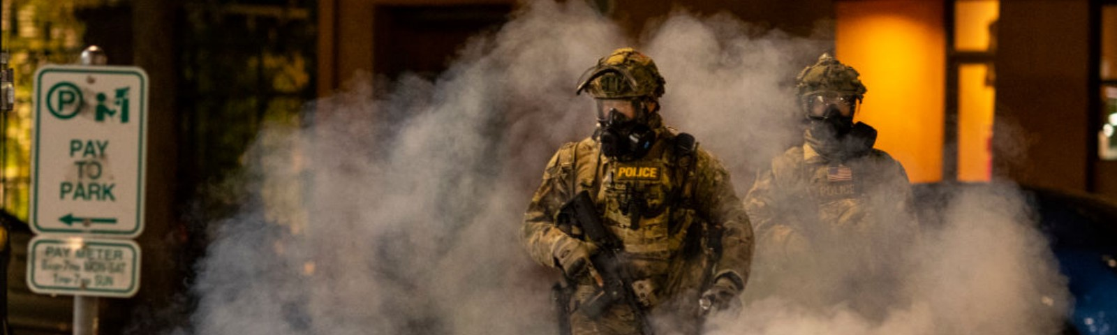 Federal officers in camoflague walk amidst tear gas while quelling protestors in Portland.